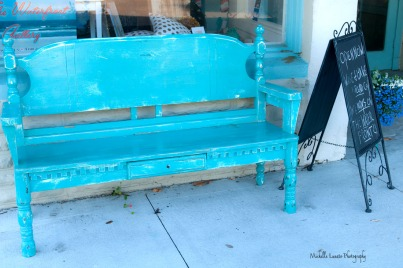 A rather attractive bench in front of a shop.